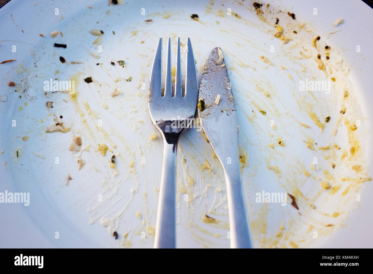 An empty plate after a meal, scraps of food and knife and fork placed together. - Stock Image