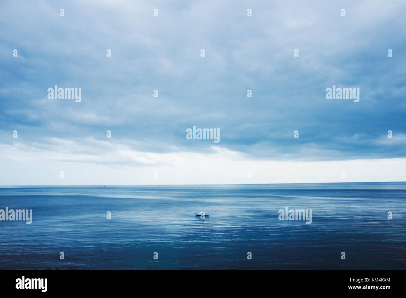 View across a calm sea to the horizon and a cloudy sky. A small yacht, day boat under motor power. - Stock Image