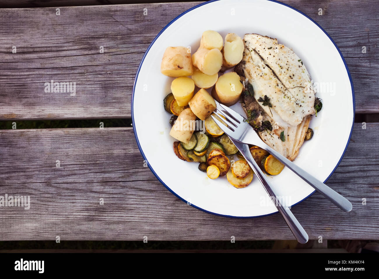 A plate of fresh grilled mackerel, cooked vegetables and potatoes on a plate with cutlery. - Stock Image