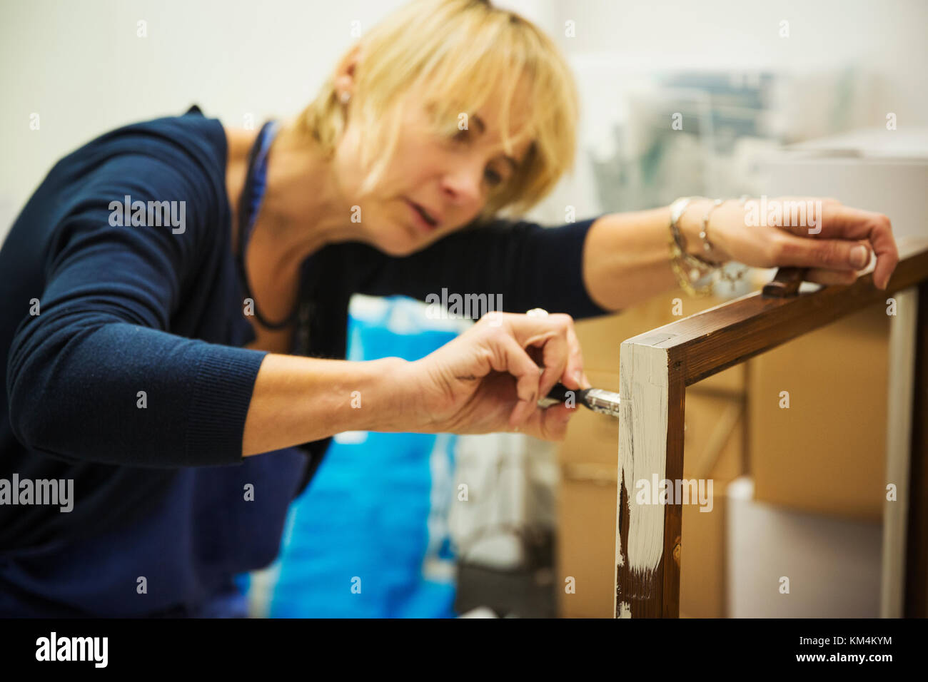 A woman working on a wooden frame with a paintbrush, upcycling wooden objects. - Stock Image