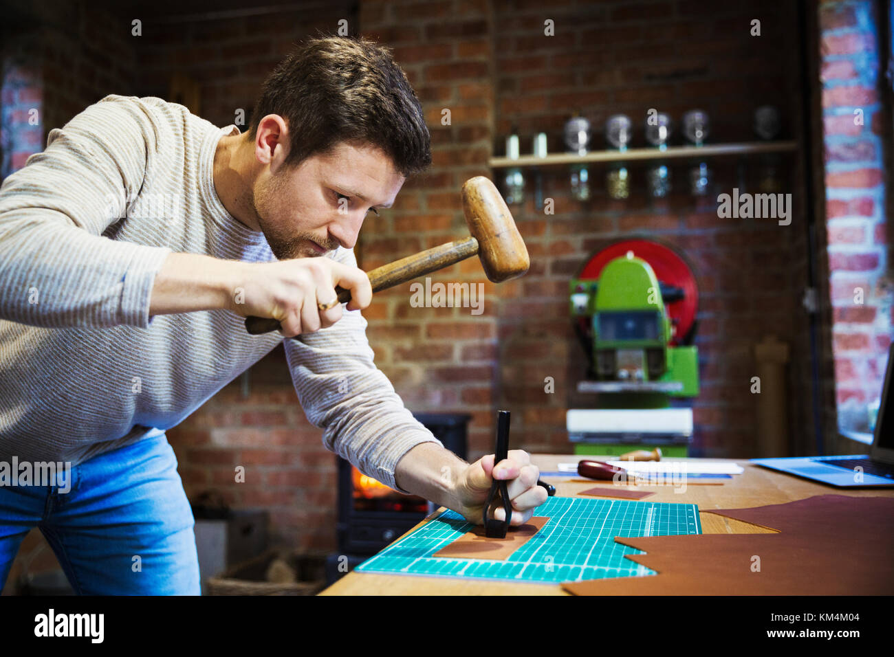 A craftsman using a hammer and pincers to hold and imprint a stamp on a piece of brown leather. - Stock Image