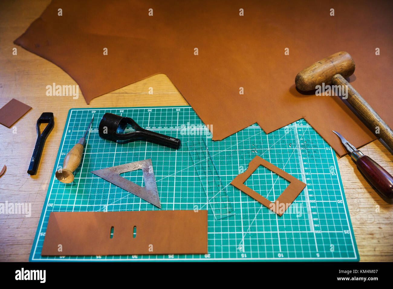 Workbench and cutting mat with a large smooth piece of brown leather, and tools for measuring cutting and stitching, - Stock Image