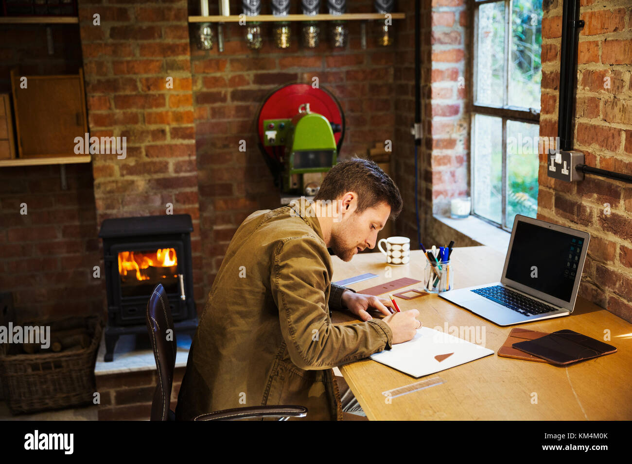 A designer seated in his leatherwork workshop, at a desk drawing on paper. A woodburning stove with a lit fire. - Stock Image