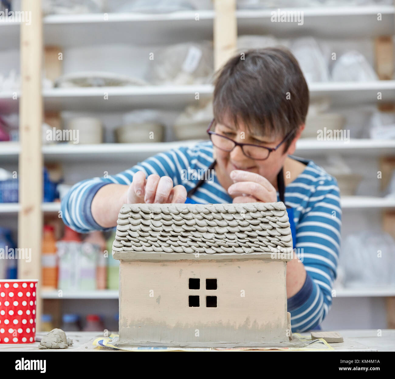 A woman potter using a small shaping tool to create the roof details for a clay model of a house. - Stock Image