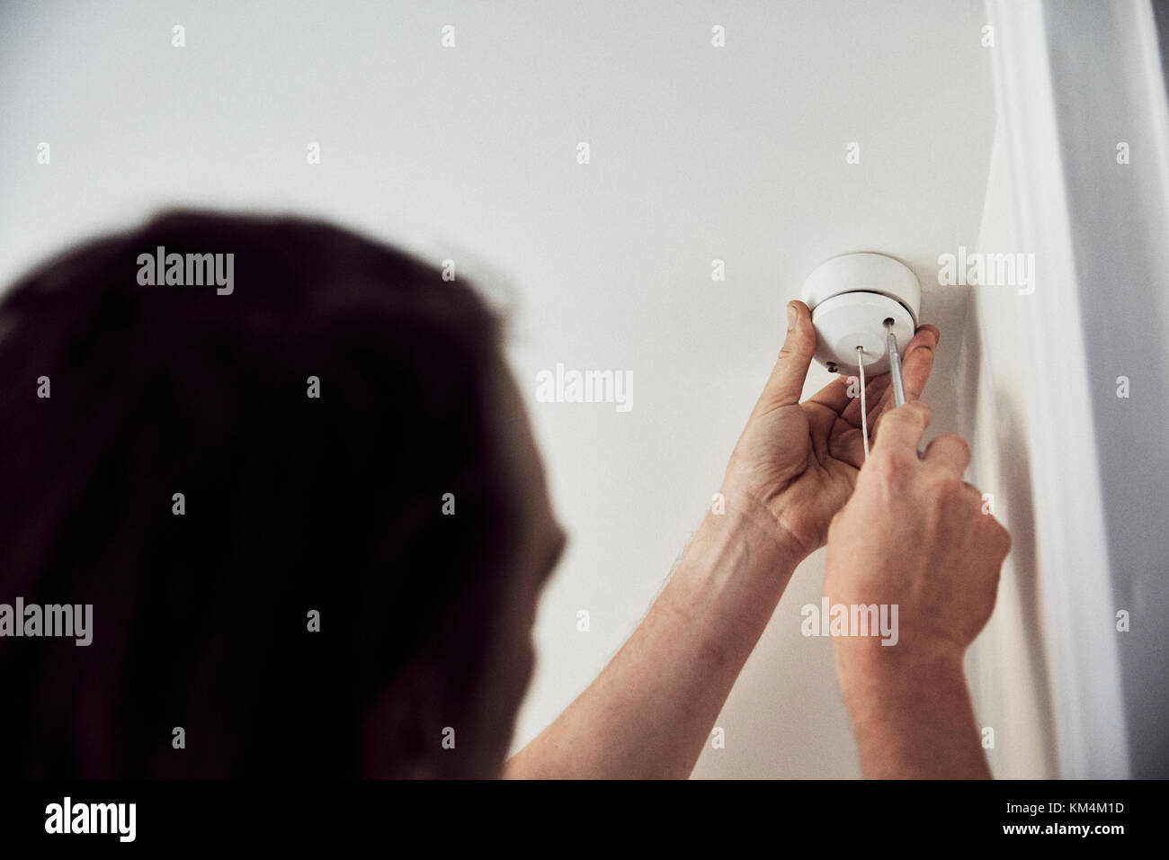 An electrician screwing the cap on a light fitting on the ceiling. - Stock Image