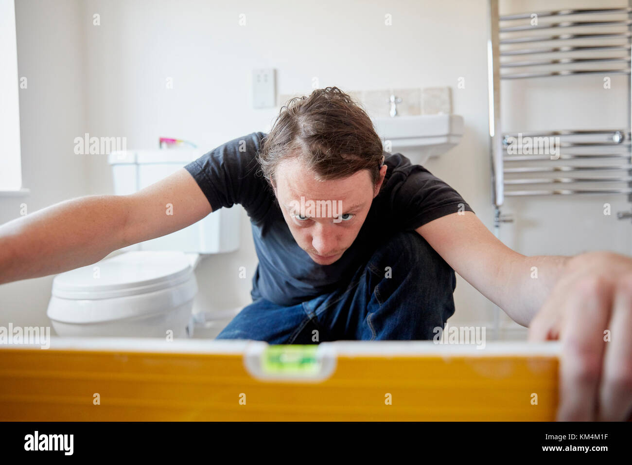 A builder using a spirit level to check his work, refurbushing a bathroom. - Stock Image