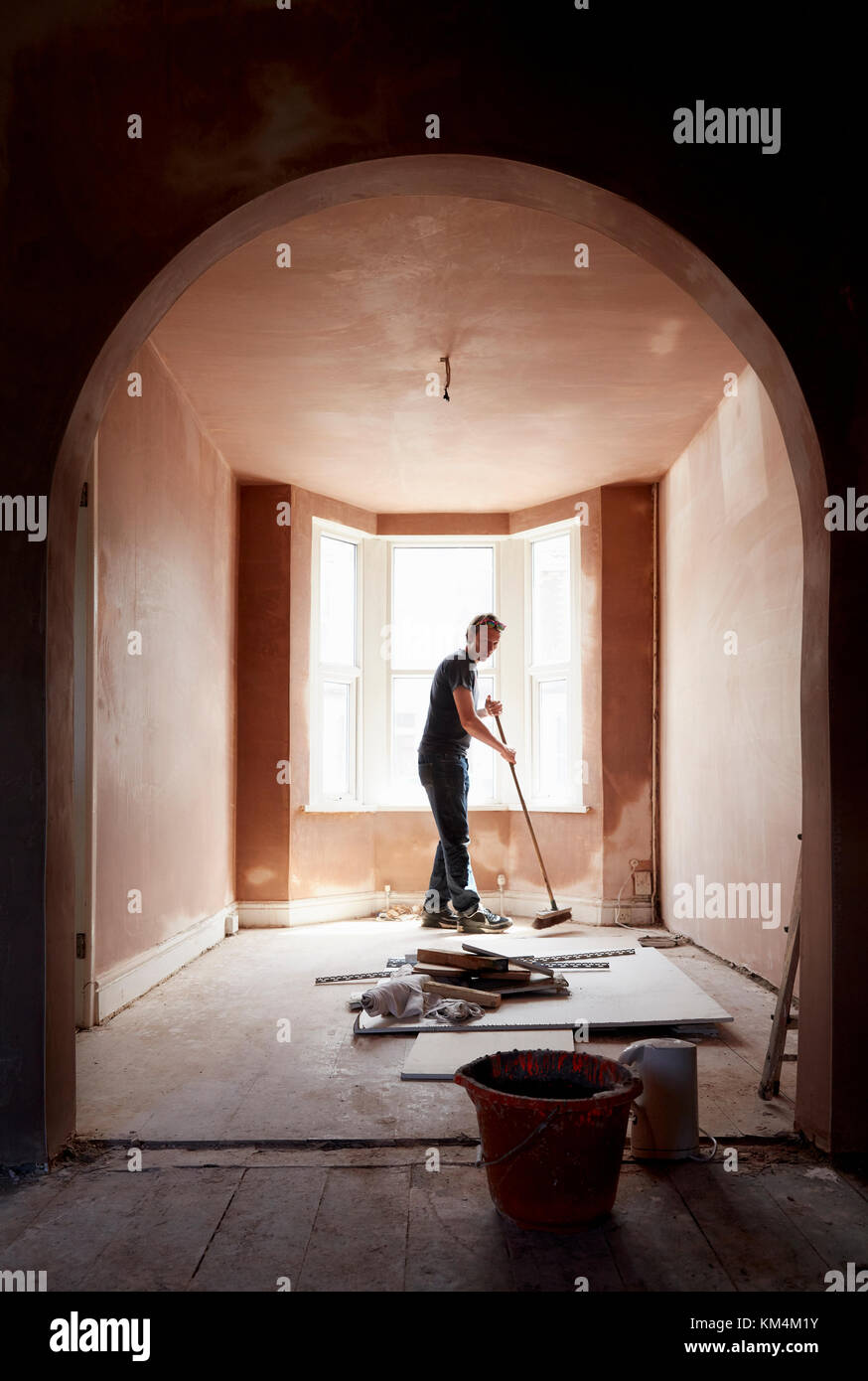 A builder sweeping and tidying up in a renovated replastered house with an archway. - Stock Image