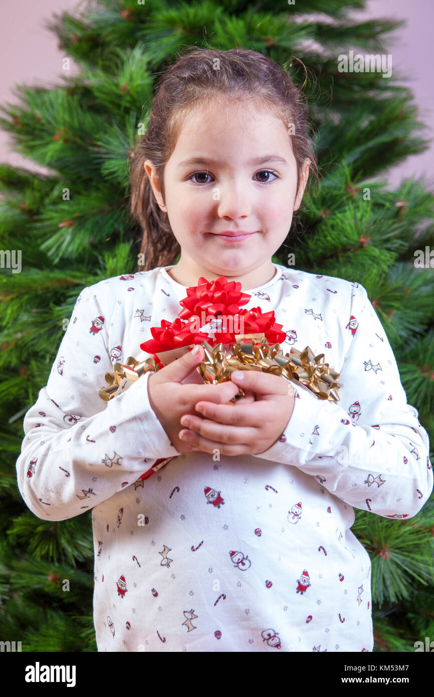 Merry Christmas and Happy New Year. Smiling little girl with a lot of ribbons for Christmas tree decoration. She - Stock Image