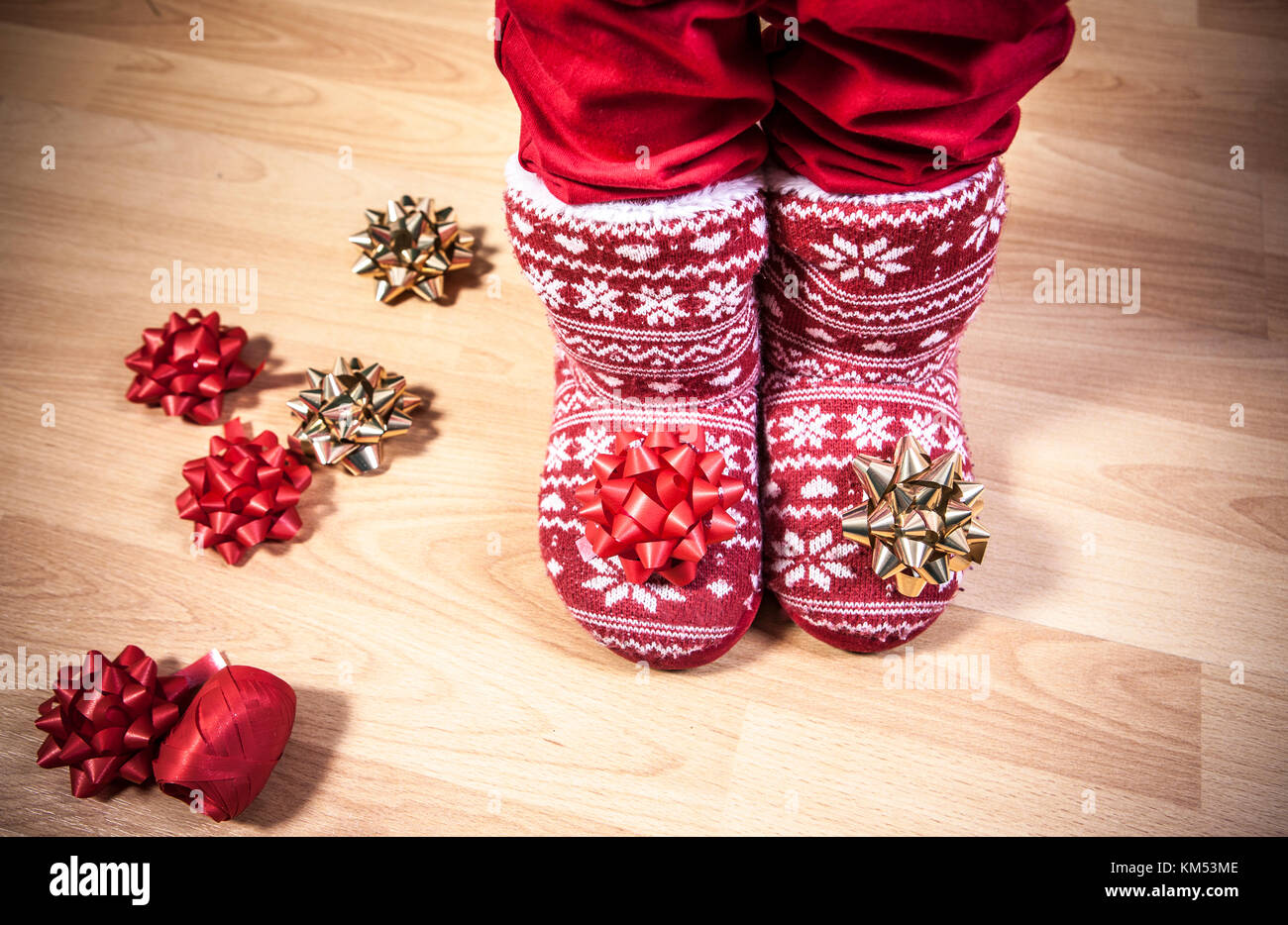Red knitted boots with fur full of ribbons over wooden floor. Christmas staff concept - Stock Image