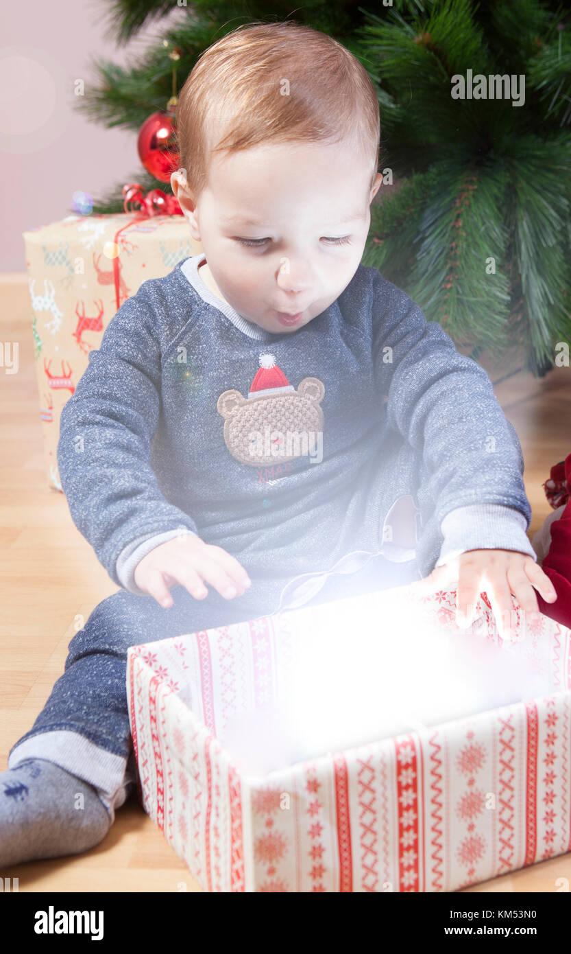 Little baby boy opening presents close to Christmas tree. He is illuminated by magical light from gift box - Stock Image