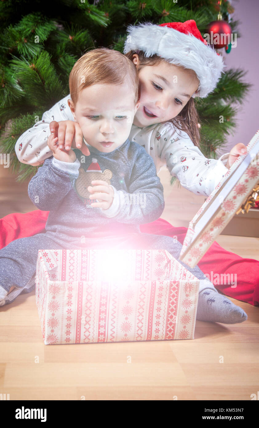 Little brothers opening their presents close to Christmas tree. They are illuminated by magical light from gift - Stock Image