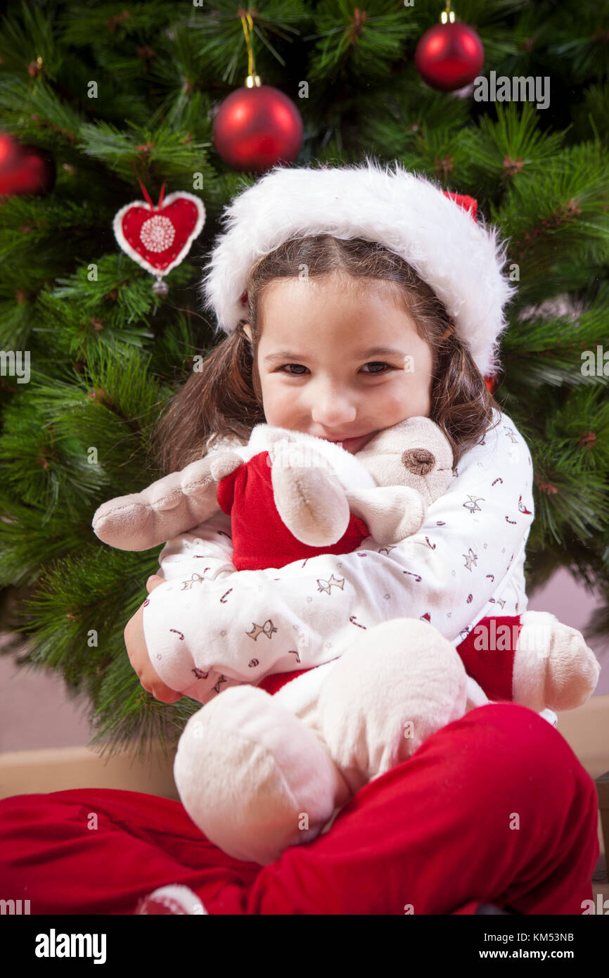 Little child girl hugging her fluffy reindeer toy close to Christmas tree. She is very, very happy - Stock Image