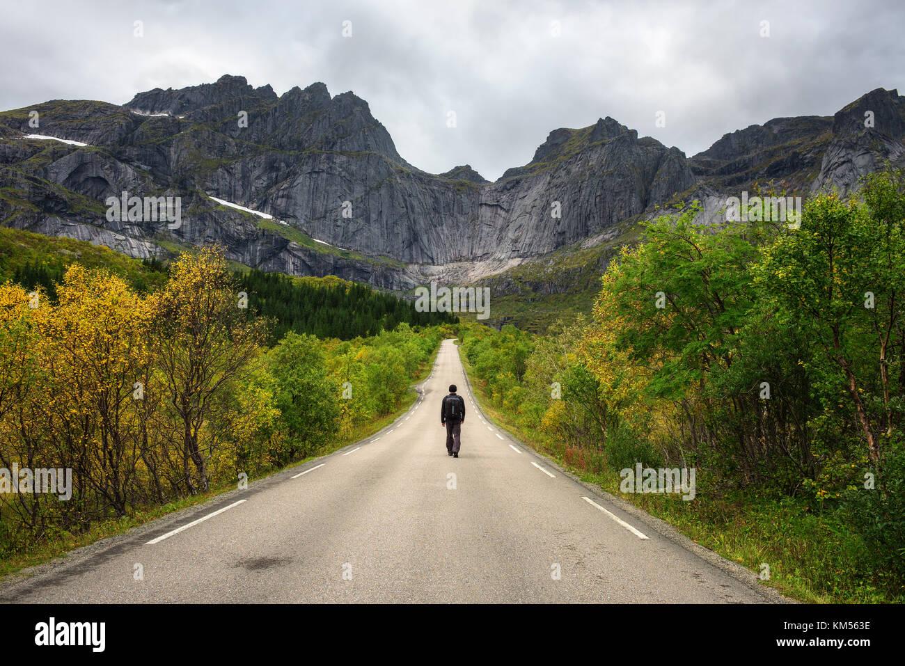 Hiker walks on a scenic road on Lofoten islands in Norway - Stock Image