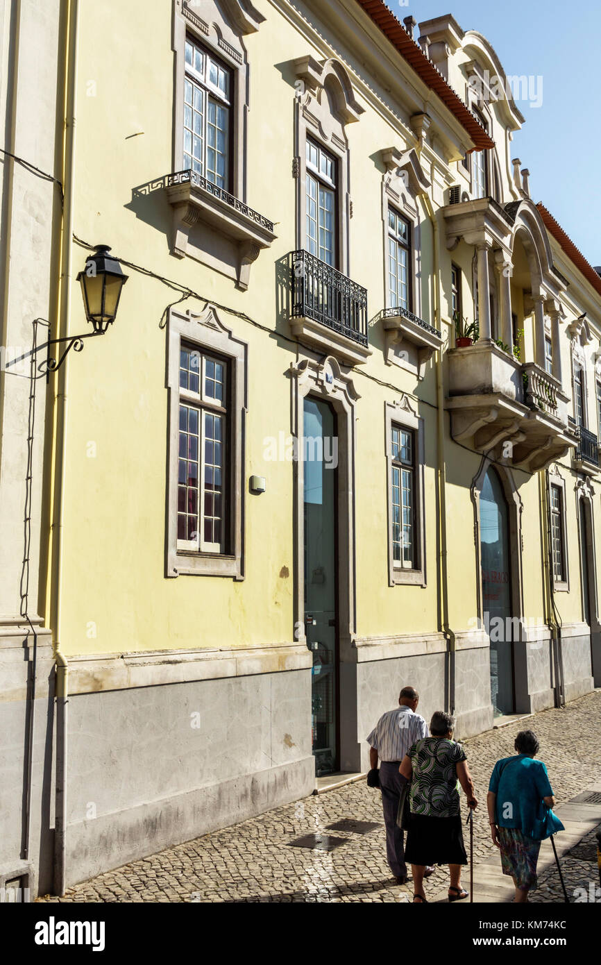 Coimbra Portugal historic center residential apartment building street alley woman man senior walking cane - Stock Image