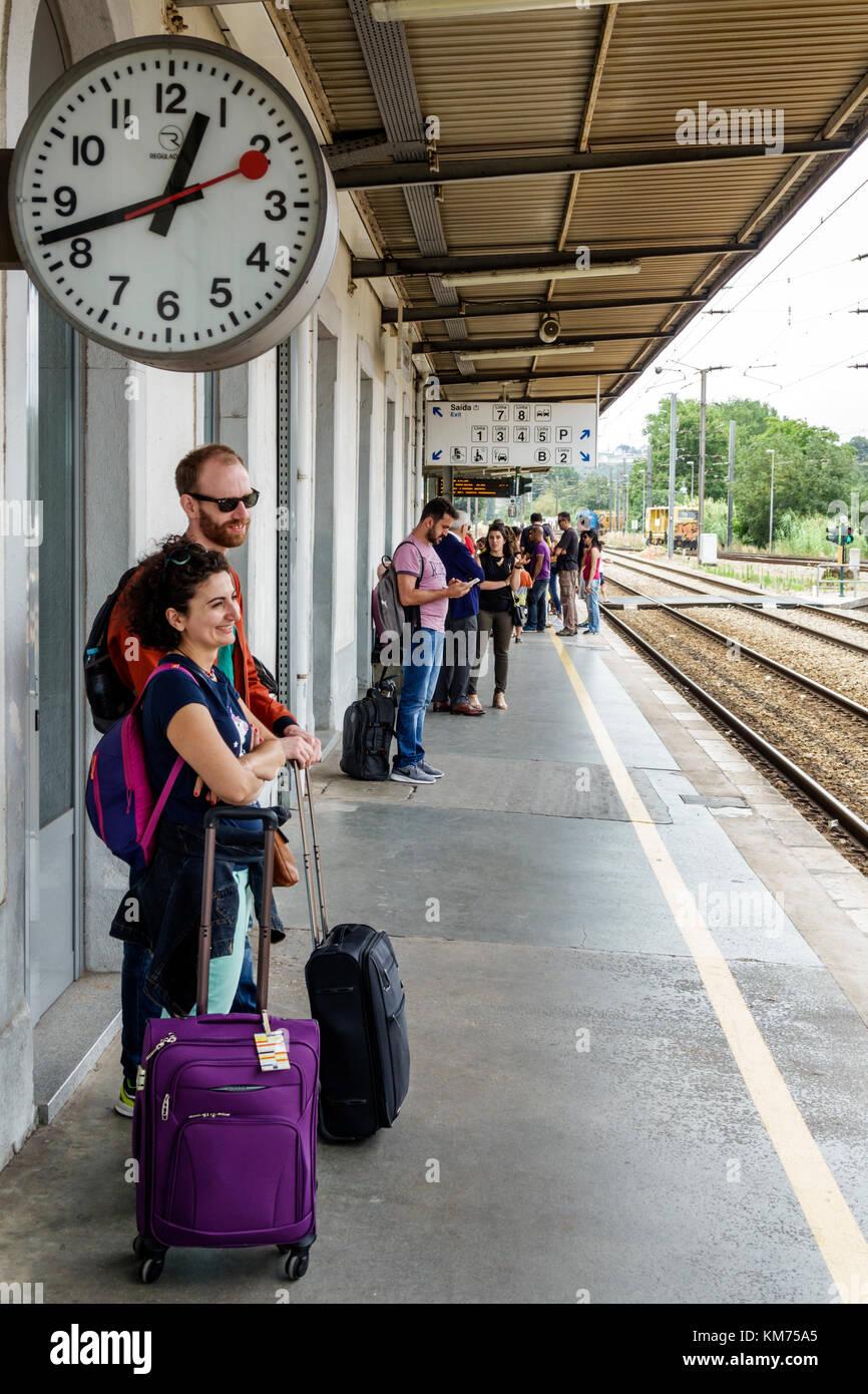Coimbra Portugal Coimbra B Comboios de Portugal railway train station platform woman man couple clock luggage - Stock Image