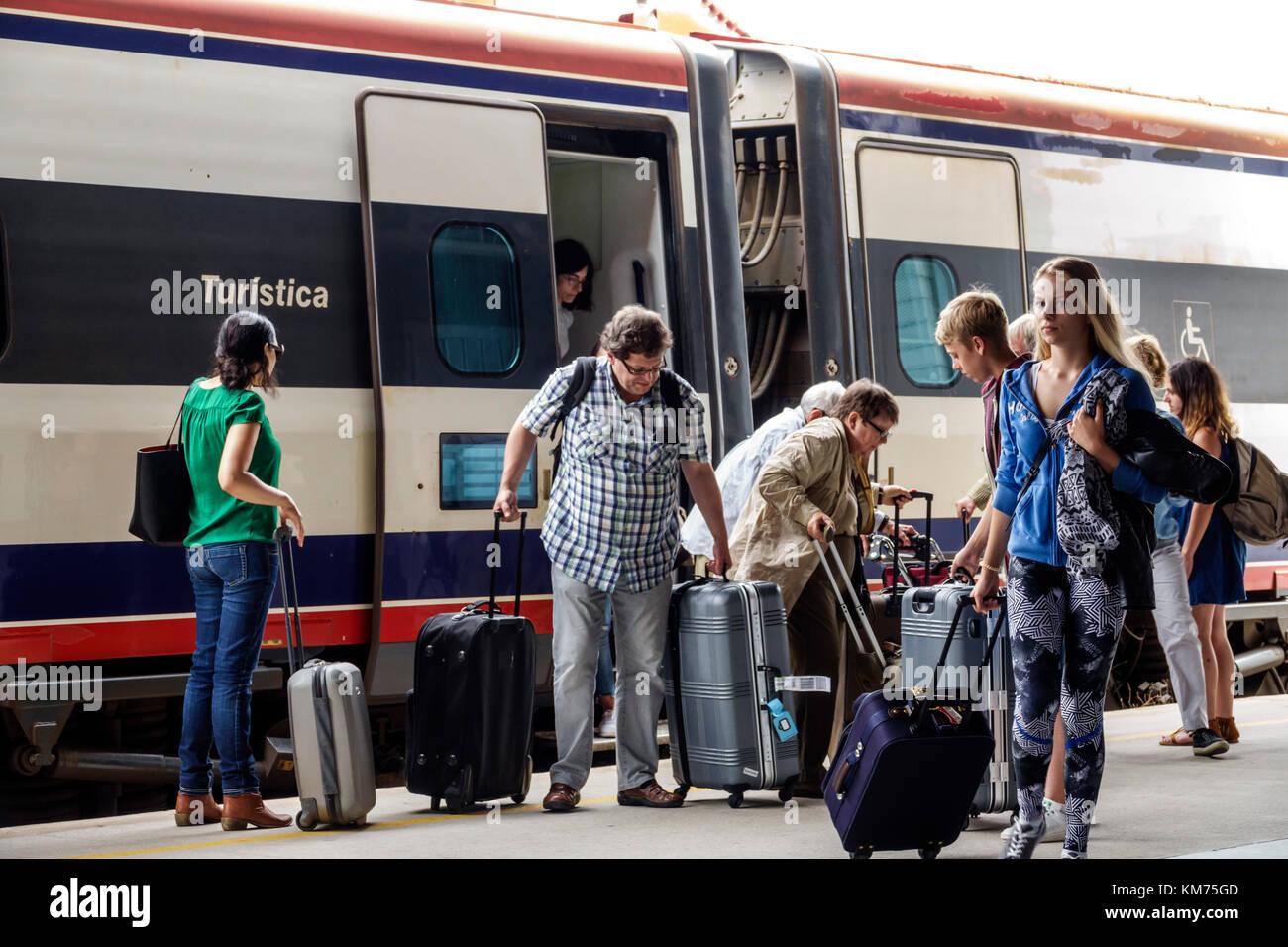 Coimbra Portugal Coimbra B Comboios de Portugal railway train station platform arrival man woman girl teen luggage - Stock Image