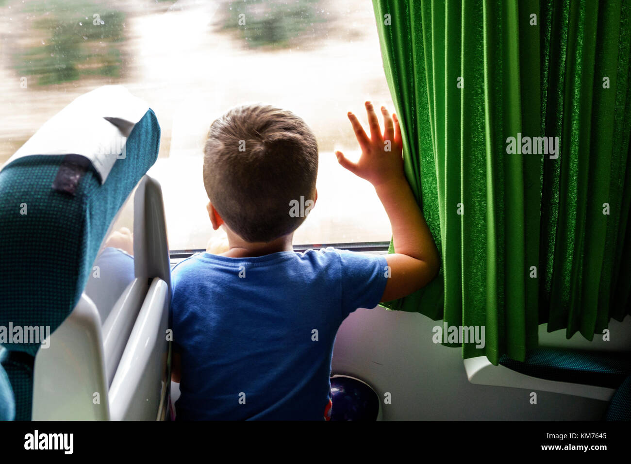 Coimbra Portugal Comboios de Portugal railway train boy rider cabin inside touching window looking out - Stock Image