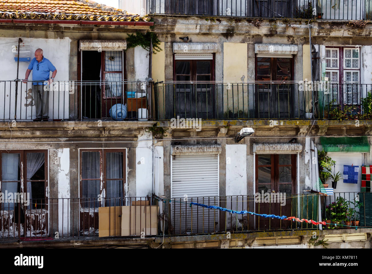 Porto Portugal historic center Ribeira neighborhood residential apartment building flats balcony man senior dilapidated - Stock Image