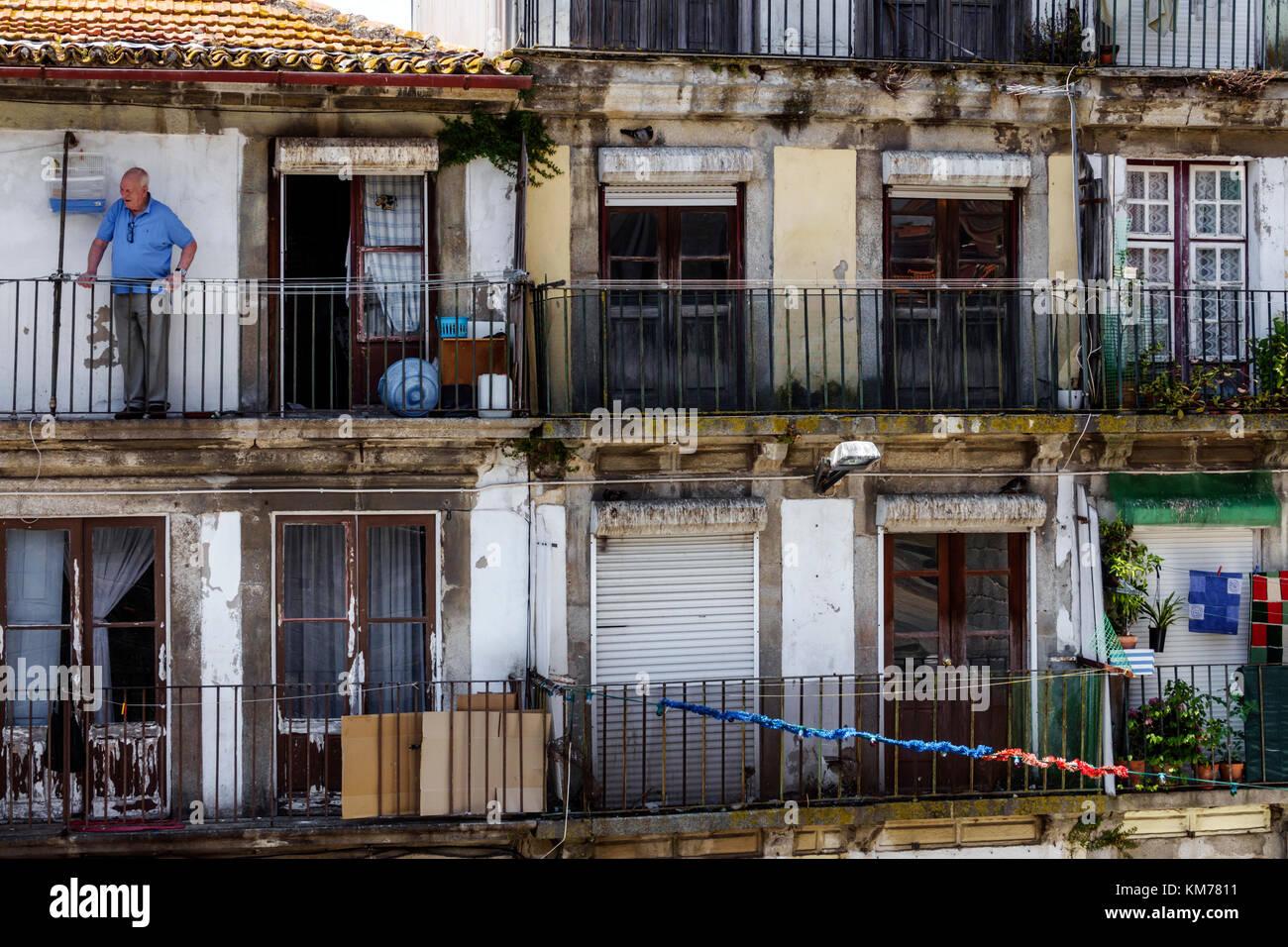 Porto Portugal historic center Ribeira neighborhood residential apartment building flats balcony man senior dilapidated - Stock Image