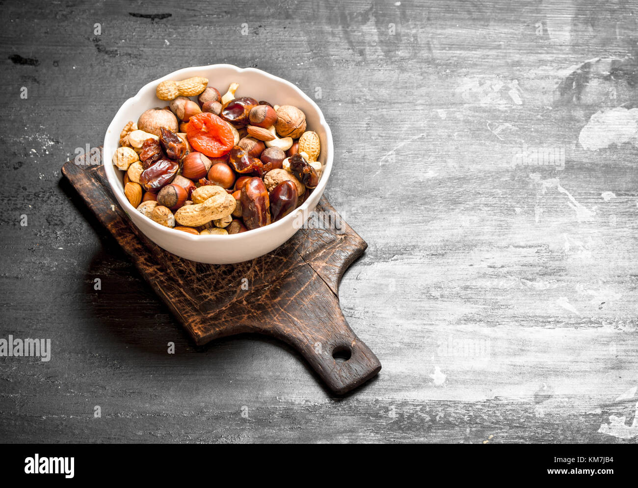 Nuts with dried fruit in a bowl. On a black chalkboard. - Stock Image