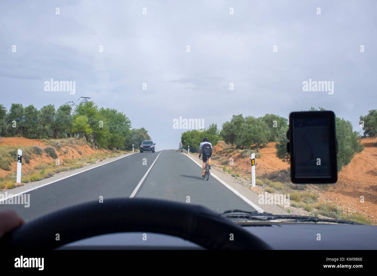 Driving slowly behind a cyclist by local road over solid line. View from the inside of the car - Stock Image