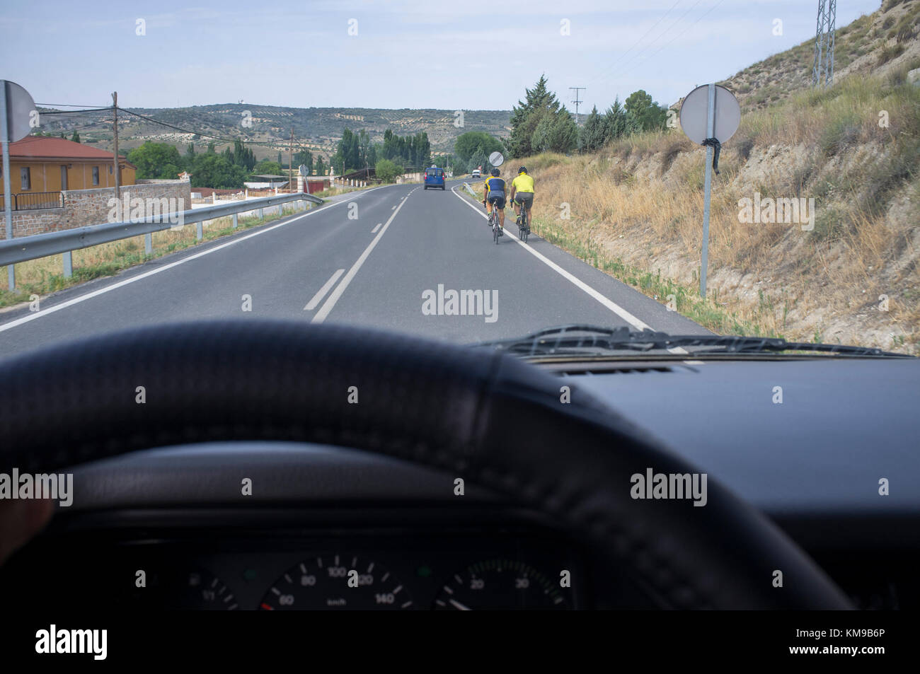 Driving slowly behind cyclists at local road. View from the inside of the car - Stock Image