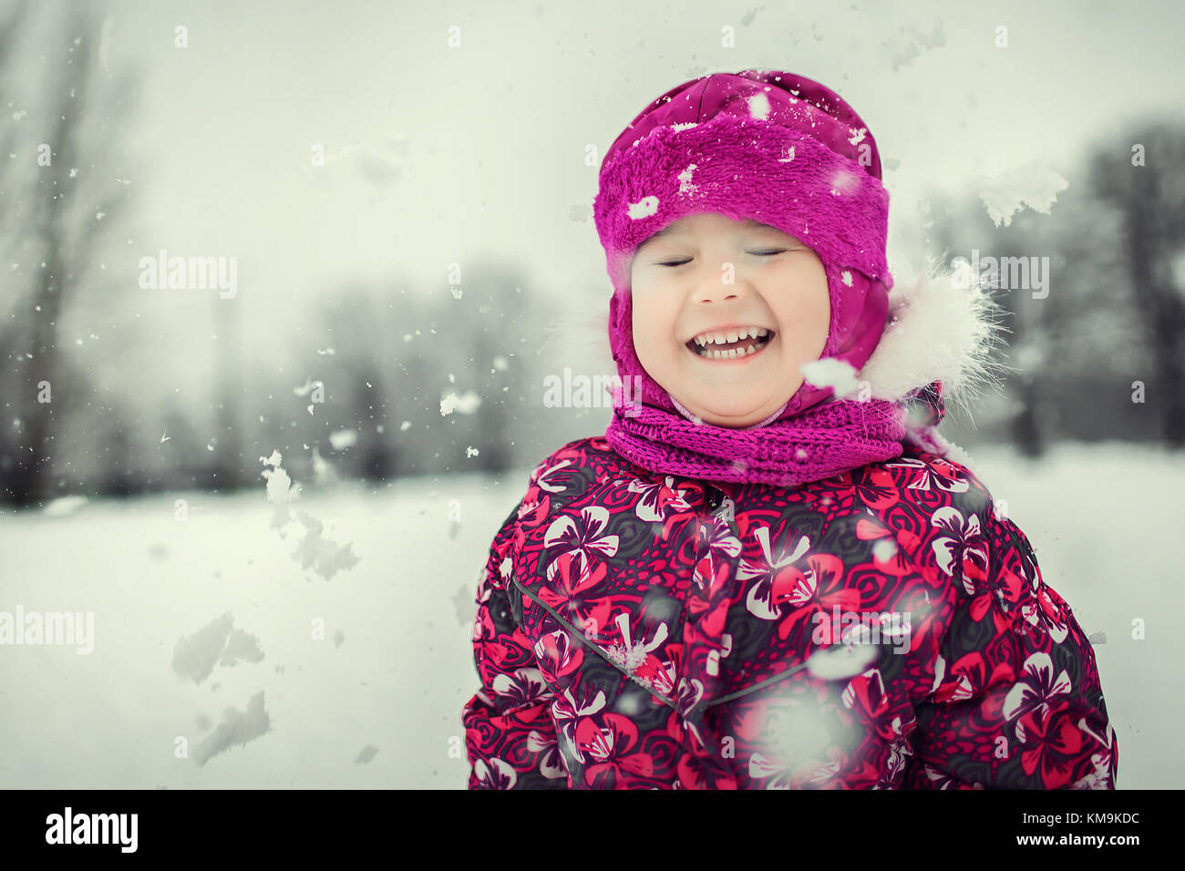 kid playing with snowflakes in winter forest - Stock Image