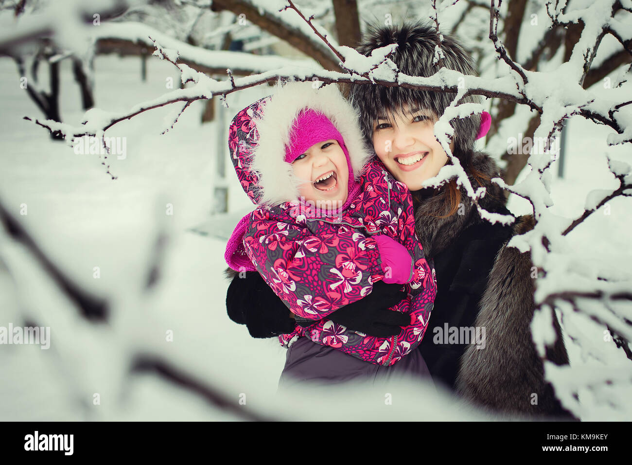 mom with kid spending time in winter park - Stock Image