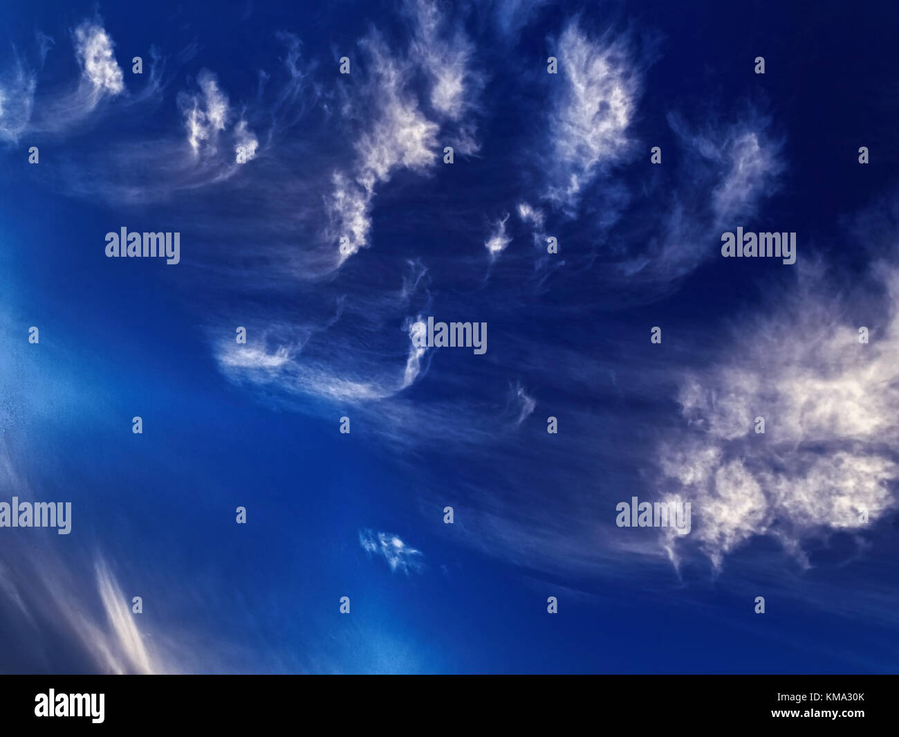 A spectacular inspirational brightly coloured atmospheric cloudy sky cloudscape featuring streaky cirrus cloud formation - Stock Image