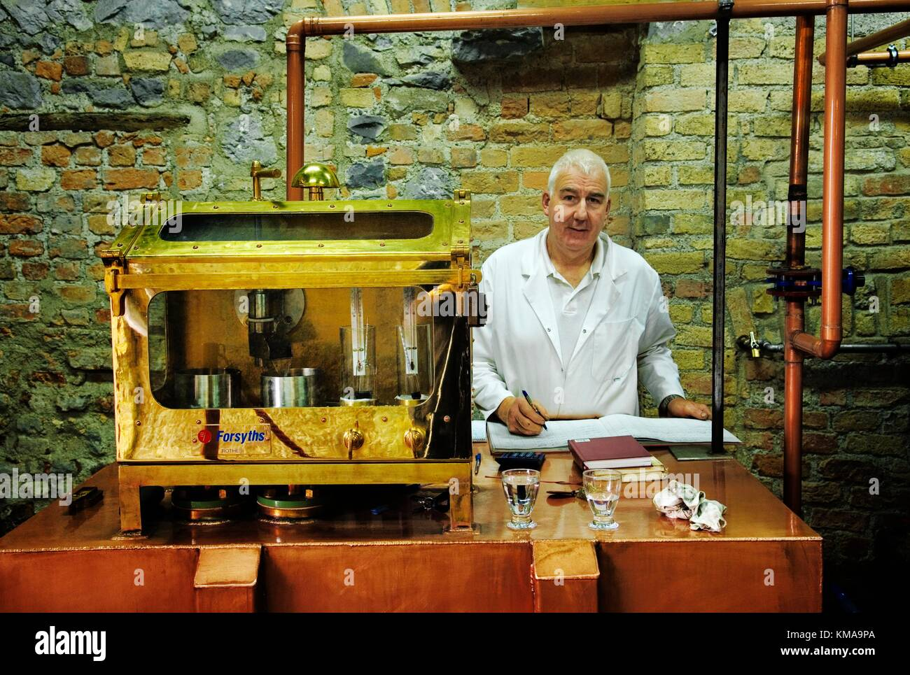 Distiller Liam O'Keefe monitors alcohol in the spirit safe. Locke's Irish whiskey Distillery, Kilbeggan, Co. Westmeath, - Stock Image