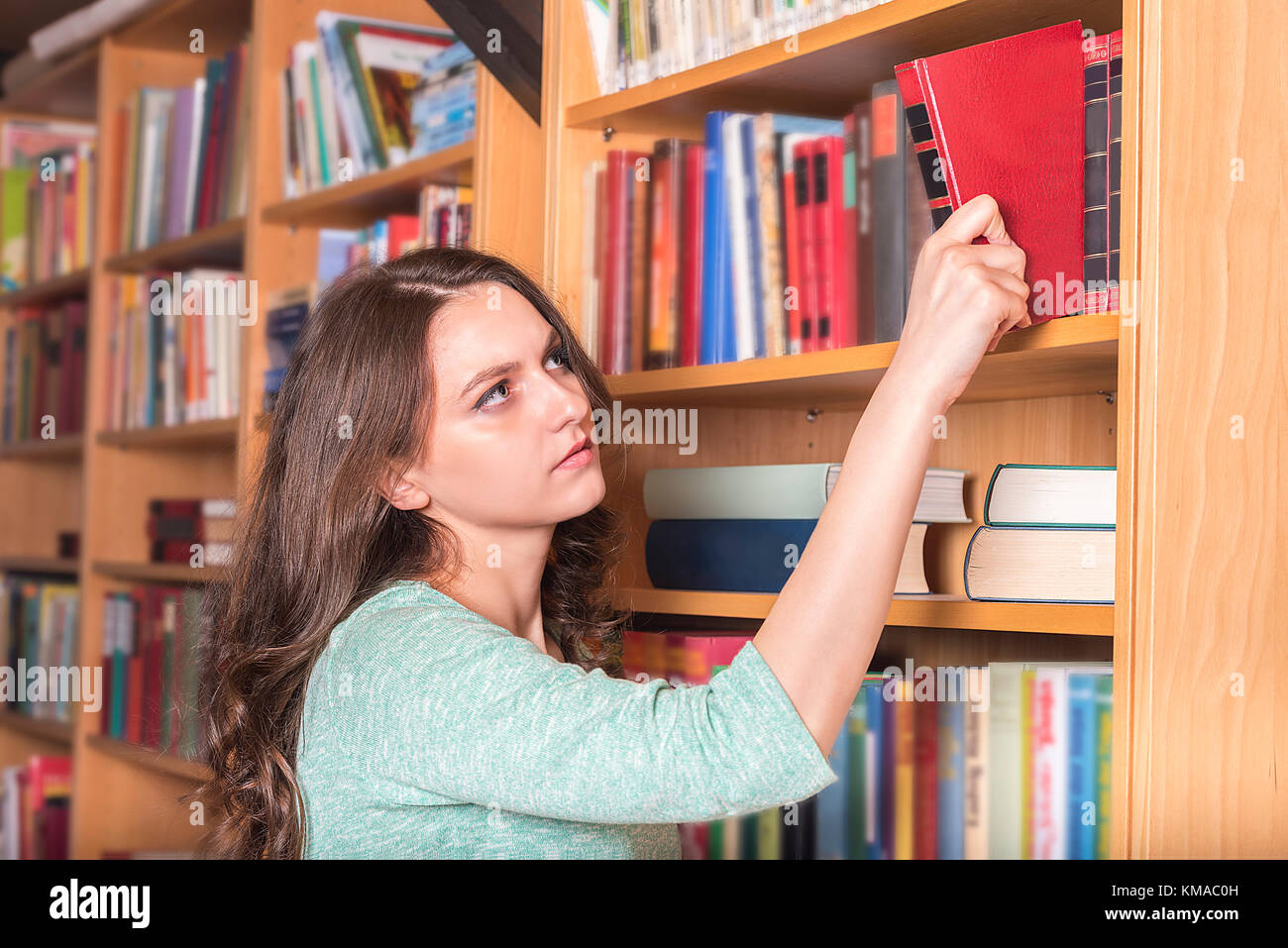 Education theme image with a beautiful girl taking a book from a library in order to study or enjoying a novel in - Stock Image