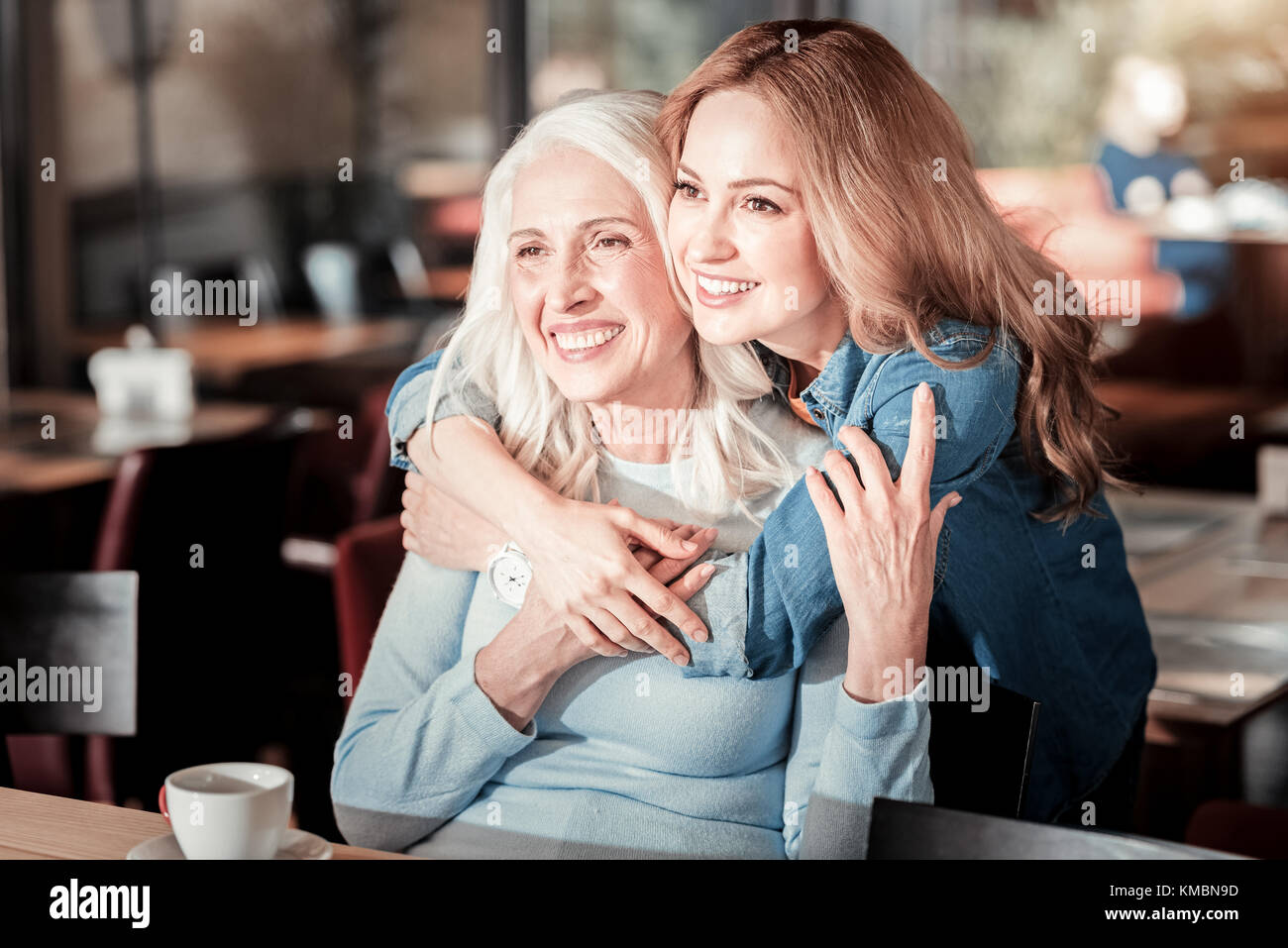 Positive senior woman laughing while her granddaughter hugging her - Stock Image