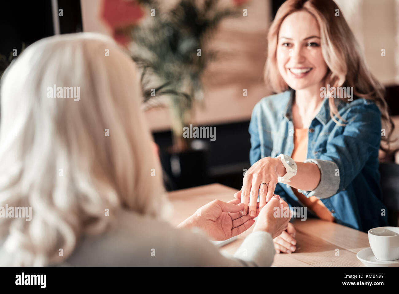 Emotional young woman showing an engagement ring to her relative - Stock Image