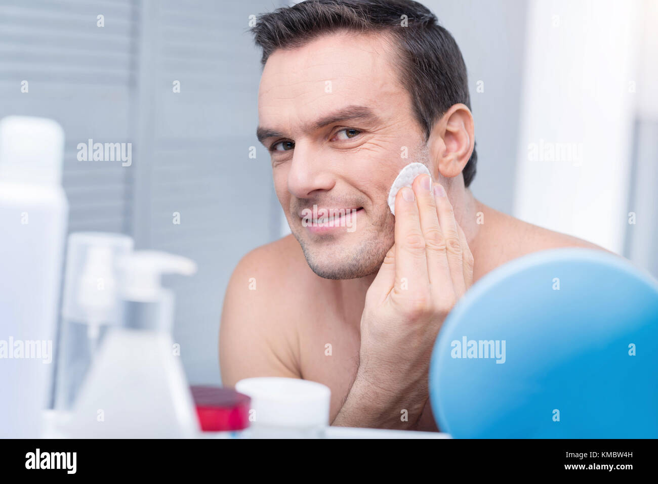 Cunning handsome man wiping his face  - Stock Image