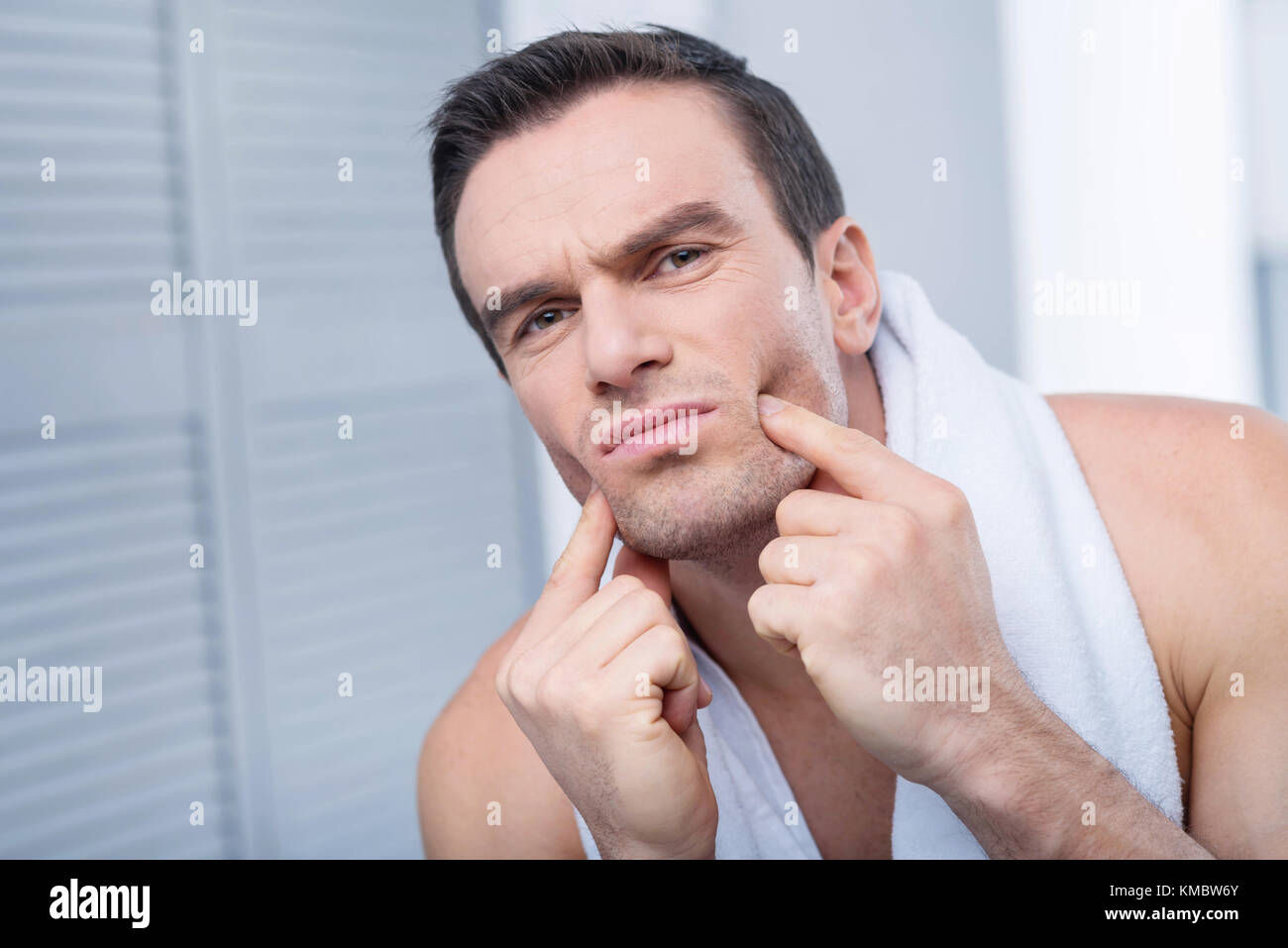 Adorable gloomy man  evaluating difference  - Stock Image