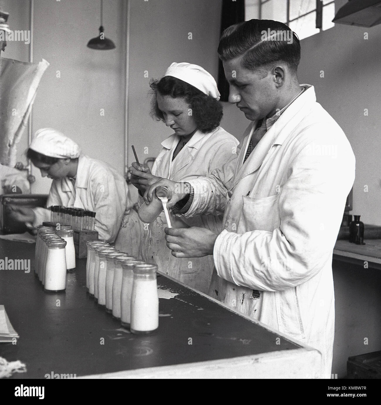 1950s, historical, male and female lab technicians in white coats working at a diary checking samples of milk taken - Stock Image