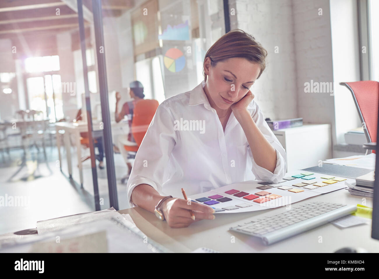 Female design professional reviewing color swatches in office - Stock Image