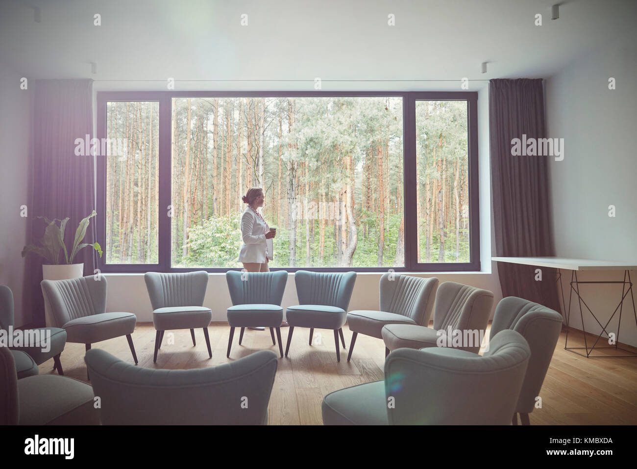 Pensive woman looking out windows at tress in group therapy room - Stock Image