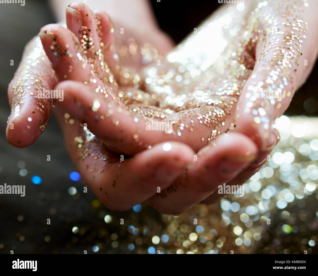 Close up hands cupping gold glitter - Stock Image