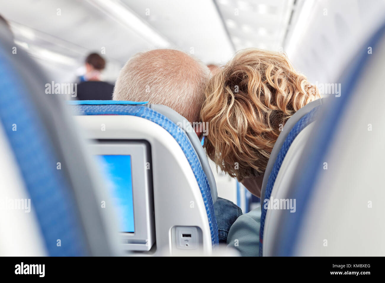 Rear view affectionate mature couple leaning on airplane - Stock Image