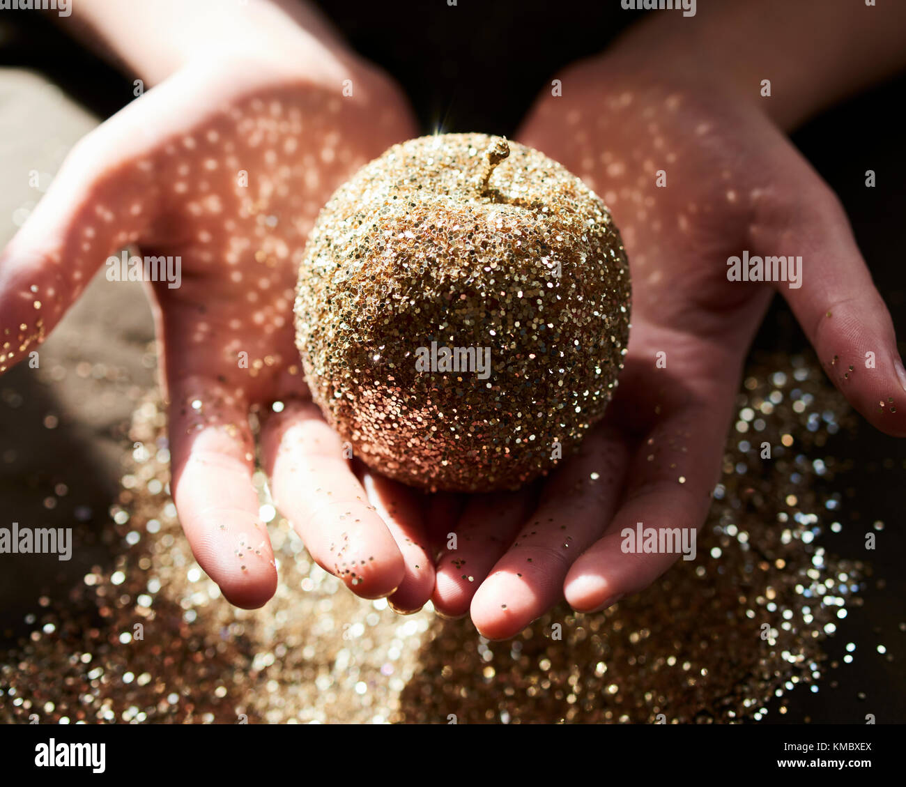 Hands cupping golden glitter apple - Stock Image