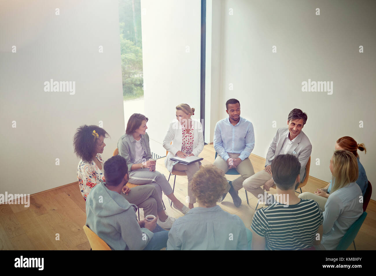 People talking in a circle in group therapy session - Stock Image