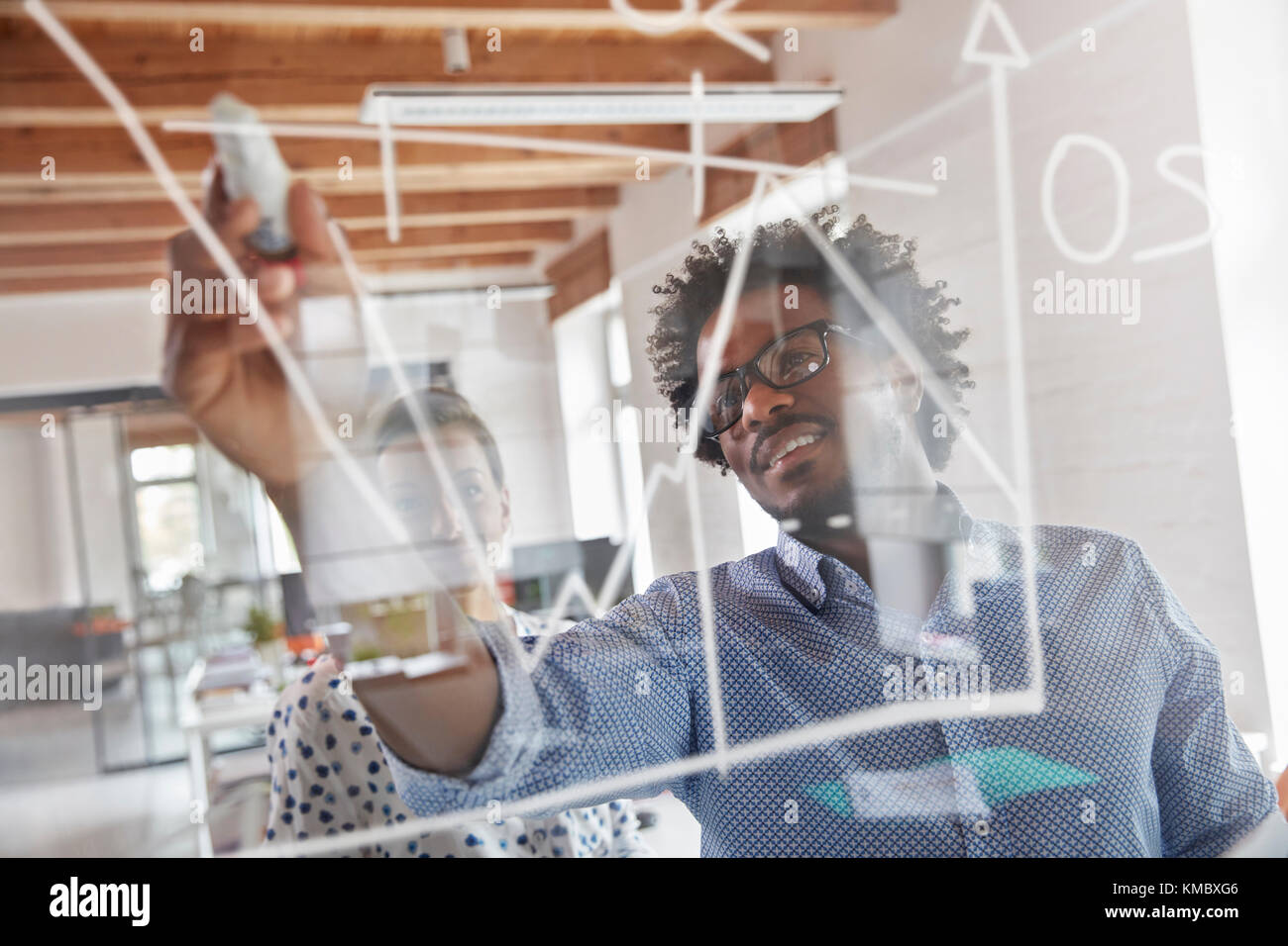 Business people drawing graph on window in office - Stock Image