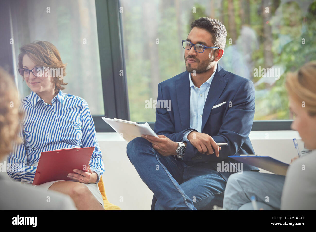 Attentive man with clipboard listening in group therapy session - Stock Image