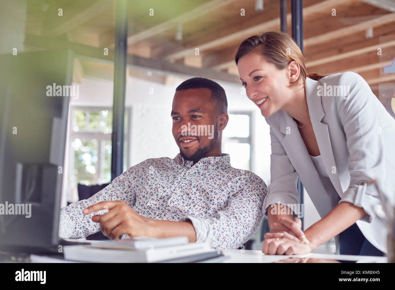 Businessman and businesswoman working at computer in office - Stock Image