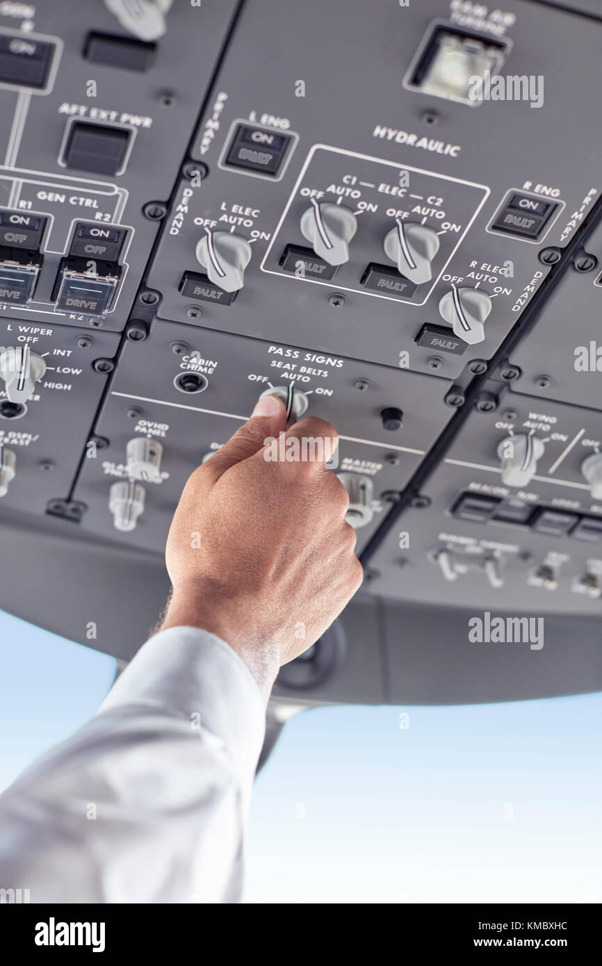 Pilot adjusting control instruments in airplane cockpit - Stock Image
