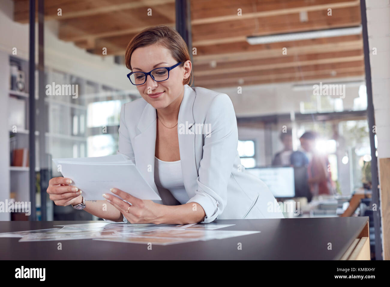 Female design professional reviewing photograph proofs in office - Stock Image