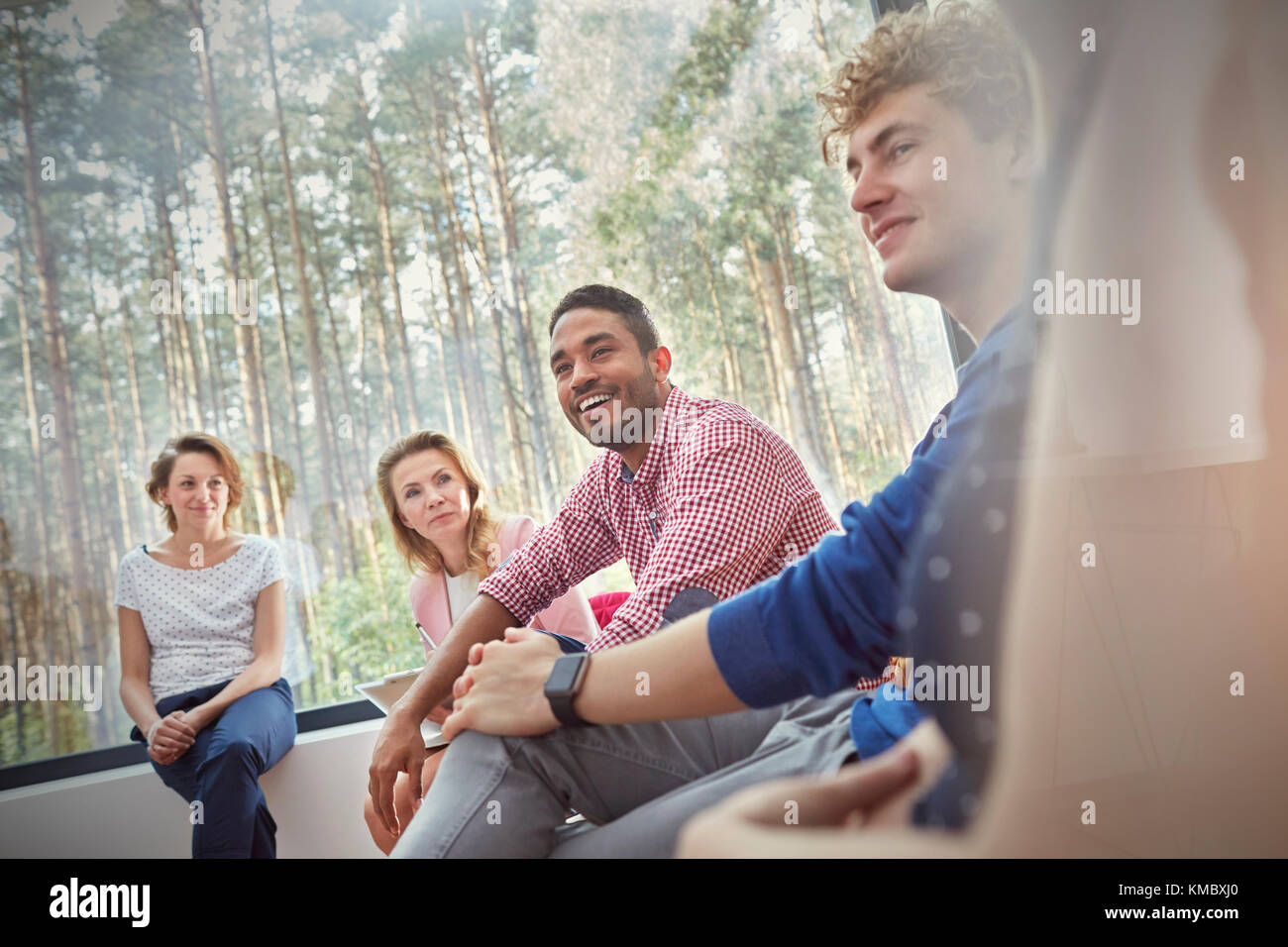 Smiling people listening in group therapy session - Stock Image