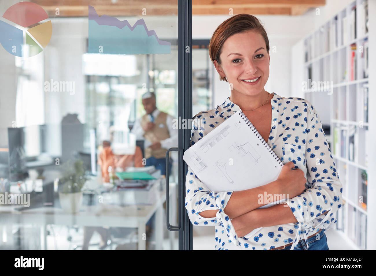 Portrait confident businesswoman with notebook in office - Stock Image