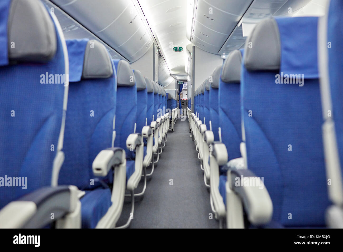 Empty blue seats in a row in airplane - Stock Image